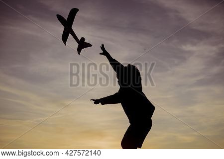 Child With Airplane Dreams Of Traveling In Summer In Nature At Sunset. Active Child Playing. Childho