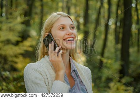 Phone Happy Outdoor. Blonde Woman Rejoicing And Holding Mobile Phone In Hands. Happy Woman Using Sma