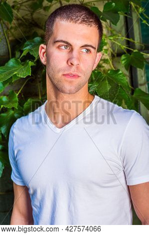 Portrait Of A Young Man, Wearing A White V-neck T-shirt, Short Hair. The Background Is Green Ivy Lea