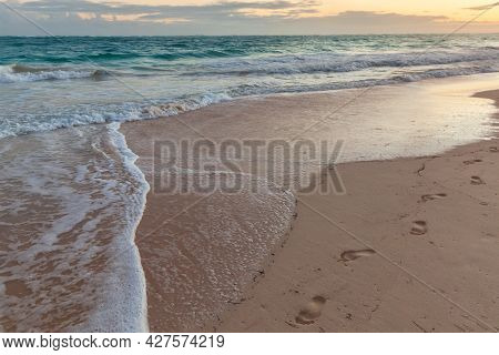 Colorful Sunrise At The Beach. Landscape With Bare Footprints Over Wet Sandy Atlantic Ocean Coast. D