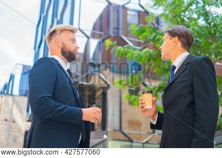 Confident businessman and his colleague in front of modern office building. Financial investors are talking outdoor. Banking and business.