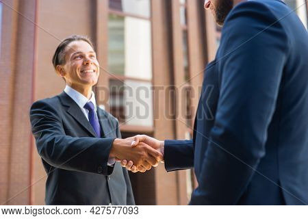 Confident businessman and his colleague are shaking hands in front of modern office building. Financial investors outdoor. Banking and business.