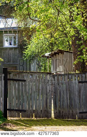 Scenic View Of An Old Wooden Fence With A Gate Against The Background Of A Wooden Two-story House Of
