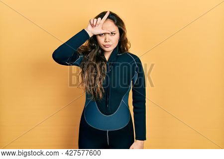 Young hispanic girl wearing diver neoprene uniform making fun of people with fingers on forehead doing loser gesture mocking and insulting.