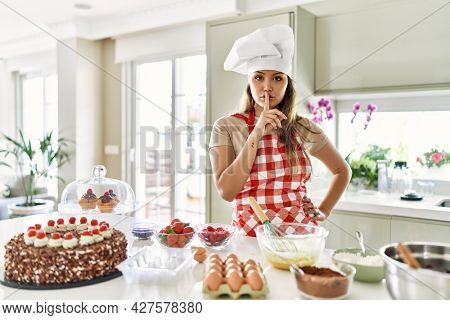Beautiful young brunette pastry chef woman cooking pastries at the kitchen asking to be quiet with finger on lips. silence and secret concept.