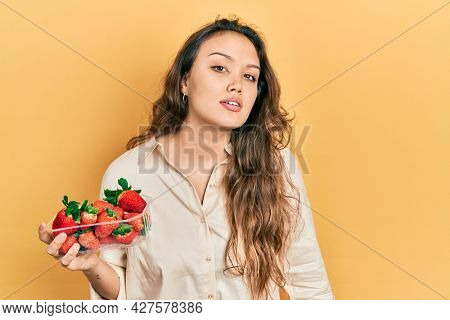 Young hispanic girl holding strawberries looking sleepy and tired, exhausted for fatigue and hangover, lazy eyes in the morning.