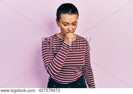 Beautiful hispanic woman with short hair wearing casual striped sweater feeling unwell and coughing as symptom for cold or bronchitis. health care concept.