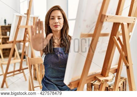 Young latin artist woman painting at art studio with open hand doing stop sign with serious and confident expression, defense gesture