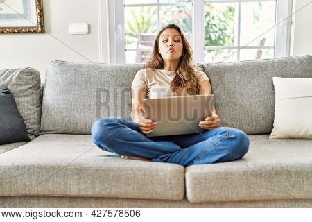 Beautiful young brunette woman sitting on the sofa using computer laptop at home making fish face with lips, crazy and comical gesture. funny expression.