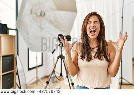 Young latin woman standing at photography studio celebrating mad and crazy for success with arms raised and closed eyes screaming excited. winner concept