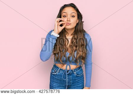 Young hispanic girl wearing casual clothes mouth and lips shut as zip with fingers. secret and silent, taboo talking