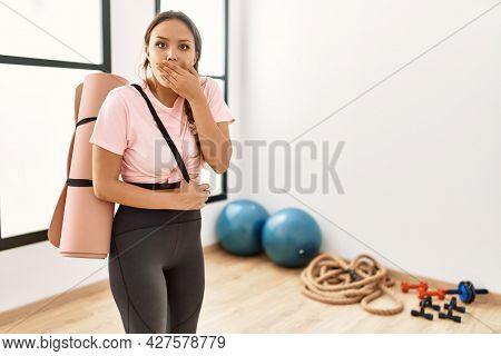 Young beautiful woman at the gym wearing sportswear holding yoga mat covering mouth with hand, shocked and afraid for mistake. surprised expression