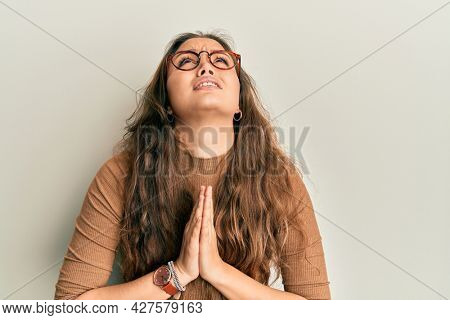 Young hispanic girl wearing casual clothes and glasses begging and praying with hands together with hope expression on face very emotional and worried. begging.