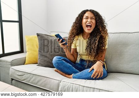 Beautiful hispanic woman sitting on the sofa at home using smartphone angry and mad screaming frustrated and furious, shouting with anger. rage and aggressive concept.