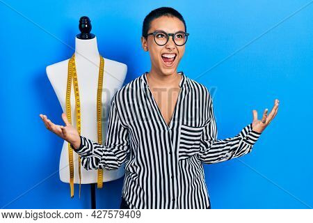 Beautiful hispanic woman with short hair standing by manikin crazy and mad shouting and yelling with aggressive expression and arms raised. frustration concept.