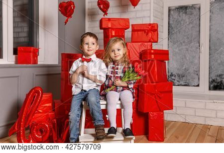 Boy And Girl Give A Gift On Valentine Day. Young Couple Hugging. Romantic Kiss. Beautiful Young Coup