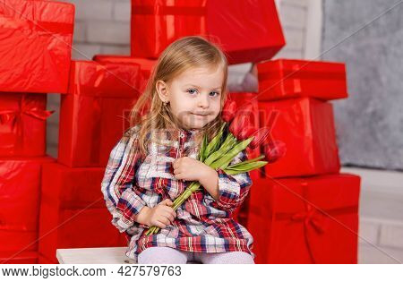 Portrait Of Cute Child With Bouquet Of Flowers In Hands. Happy Birthday Gift. Funny Surprised Little