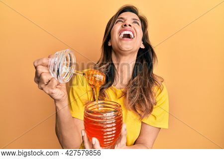 Young latin woman holding honey angry and mad screaming frustrated and furious, shouting with anger looking up.