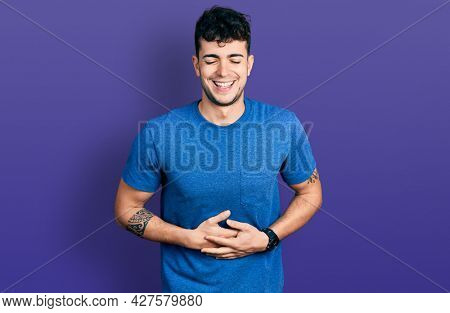 Young hispanic man wearing casual t shirt smiling and laughing hard out loud because funny crazy joke with hands on body.
