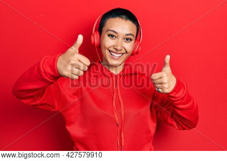 Beautiful hispanic woman with short hair listening to music using headphones approving doing positive gesture with hand, thumbs up smiling and happy for success. winner gesture.
