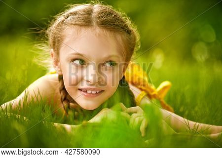 Portrait of a cute girl with pigtails lying on a green lawn and smiling. Happy summer holidays. Walk in the park.