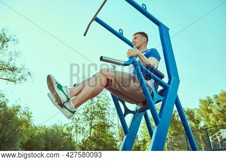 Athletic man doing abdominal exercises on sports equipment in the park.