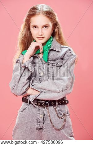 Youth fashion. Portrait of a cute teenage girl in modern denim overalls smiling at camera on a pink background.