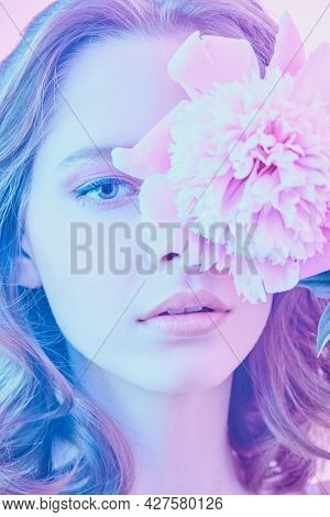 Beauty and flowers. Close-up portrait of a beautiful girl with curly hair and gentle lilac-violet make-up holding a delicate peony flower in front of her eye. Beauty, perfumery and cosmetics.