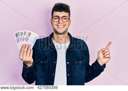 Young hispanic man holding egyptian pounds banknotes smiling happy pointing with hand and finger to the side