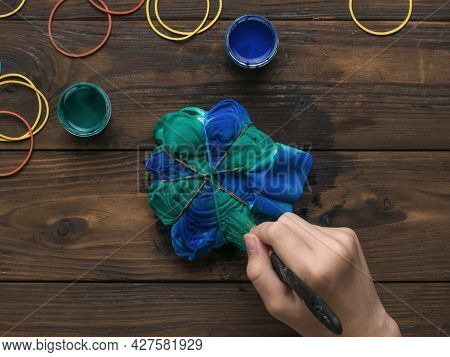 A Woman Dyes A Fabric At Home. Staining Fabric In Tie Dye Style.