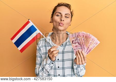 Young brunette woman holding thailand flag and baht banknotes looking at the camera blowing a kiss being lovely and sexy. love expression.