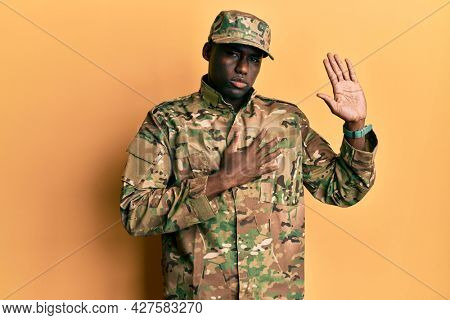 Young african american man wearing army uniform swearing with hand on chest and open palm, making a loyalty promise oath