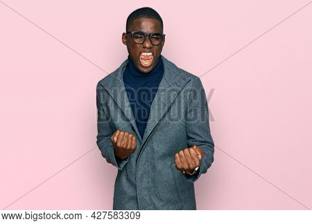 Young african american man wearing business clothes and glasses celebrating surprised and amazed for success with arms raised and eyes closed. winner concept.