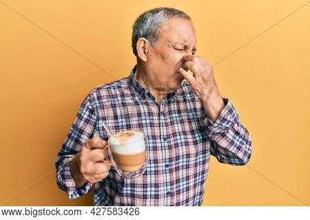 Handsome senior man with grey hair drinking a cup coffee smelling something stinky and disgusting, intolerable smell, holding breath with fingers on nose. bad smell