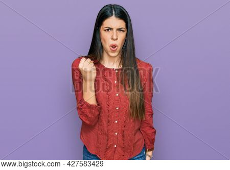 Young hispanic woman wearing casual clothes angry and mad raising fist frustrated and furious while shouting with anger. rage and aggressive concept.