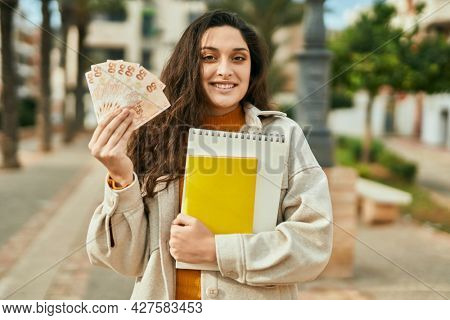 Young middle east student woman holding turkish lira banknotes at the city.