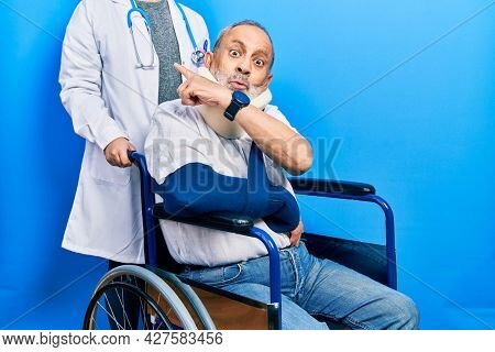 Handsome senior man with beard sitting on wheelchair with neck collar surprised pointing with finger to the side, open mouth amazed expression.