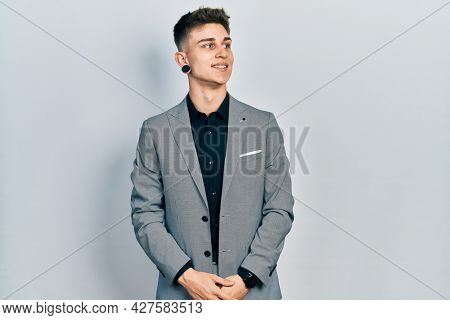 Young caucasian boy with ears dilation wearing business jacket looking away to side with smile on face, natural expression. laughing confident.