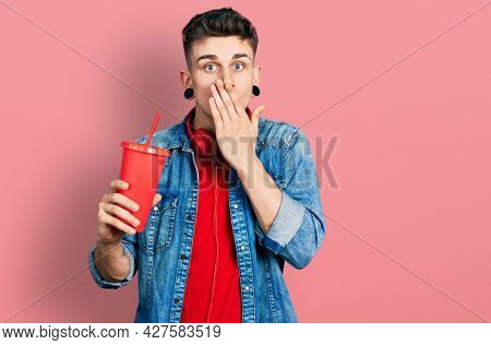 Young caucasian boy with ears dilation drinking glass of cola beverage covering mouth with hand, shocked and afraid for mistake. surprised expression