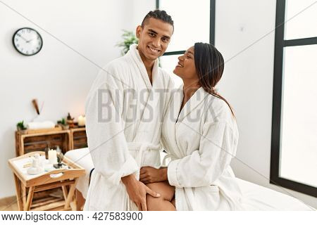 Young latin couple wearing bathrobe hugging and sitting on massage table at beauty center.