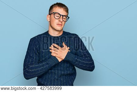 Young blond man wearing casual clothes and glasses smiling with hands on chest with closed eyes and grateful gesture on face. health concept.