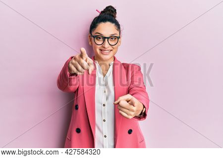 Beautiful middle eastern woman wearing business jacket and glasses pointing to you and the camera with fingers, smiling positive and cheerful