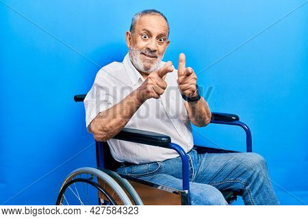 Handsome senior man with beard sitting on wheelchair pointing fingers to camera with happy and funny face. good energy and vibes.