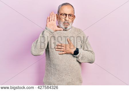 Handsome senior man with beard wearing casual sweater and glasses swearing with hand on chest and open palm, making a loyalty promise oath