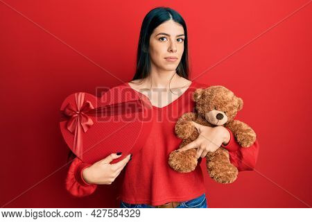 Young hispanic woman holding valentine gift relaxed with serious expression on face. simple and natural looking at the camera.