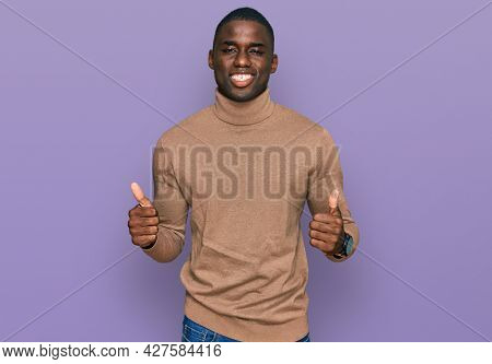 Young african american man wearing casual winter sweater success sign doing positive gesture with hand, thumbs up smiling and happy. cheerful expression and winner gesture.