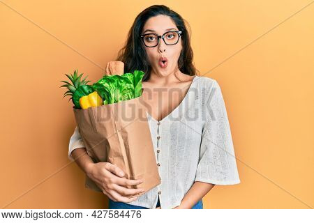 Beautiful middle eastern woman holding paper bag with groceries scared and amazed with open mouth for surprise, disbelief face