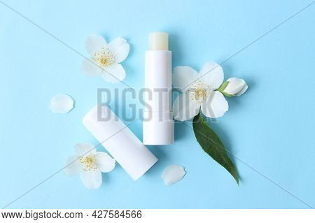 Lip Balm And Flowers On A Colored Background Close-up
