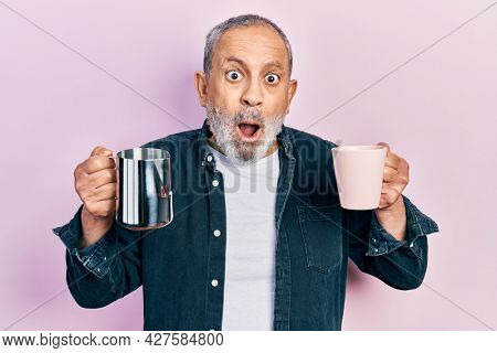 Handsome senior man with beard holding coffee and milk afraid and shocked with surprise and amazed expression, fear and excited face.