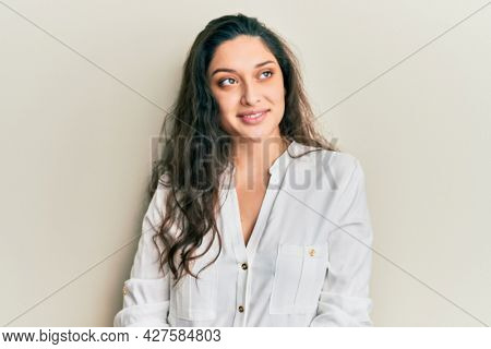 Beautiful middle eastern woman wearing casual clothes looking away to side with smile on face, natural expression. laughing confident.